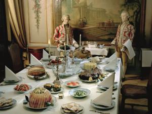 En vit damastduk, kandelabrar, en bordsplatta av fajans mitt på bordet med en skål fylld av frukt ... Det här festbordet är dukat enligt anvisningar från Johan Winbergs Kok-Bok som kom ut 1761. Här finns spansk tårta, kalvstek, kalkon, glaserad skinka, en aladåb, kronärtskockor, gröna bönor och champinjoner med kräftstjärtar. Här finns också Schiemerta, ägg som egentligen är fiskbullar. Det var högsta mode att laga rätter som såg ut att vara något annat än de egentligen. Foto: Mats Landin, Nordiska museet.